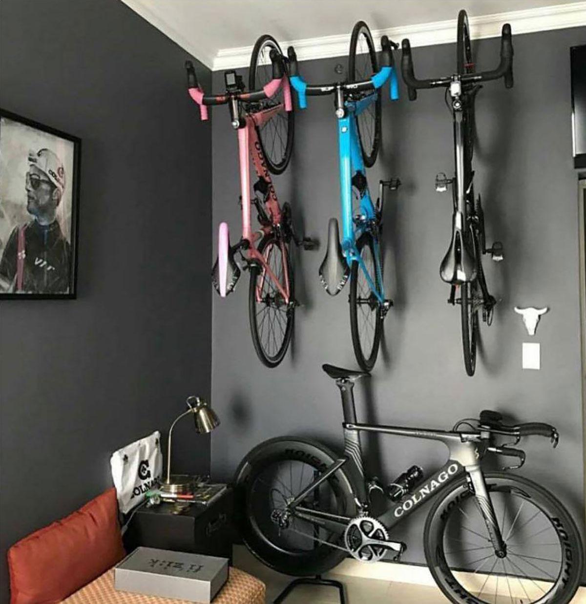 Tre bici appese al muro e una sul pavimento di una sala