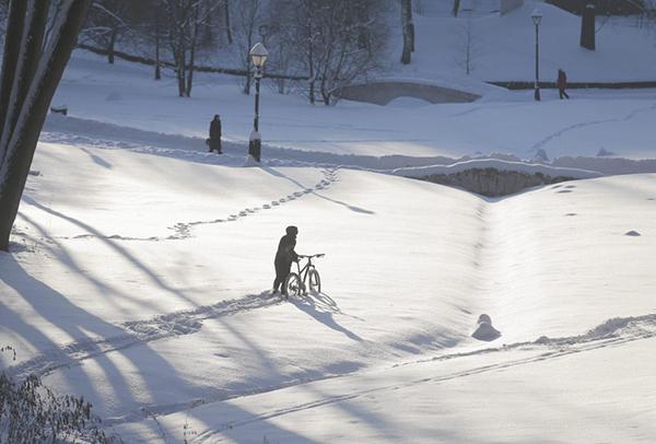 Un ciclista in un parco coperto di neve