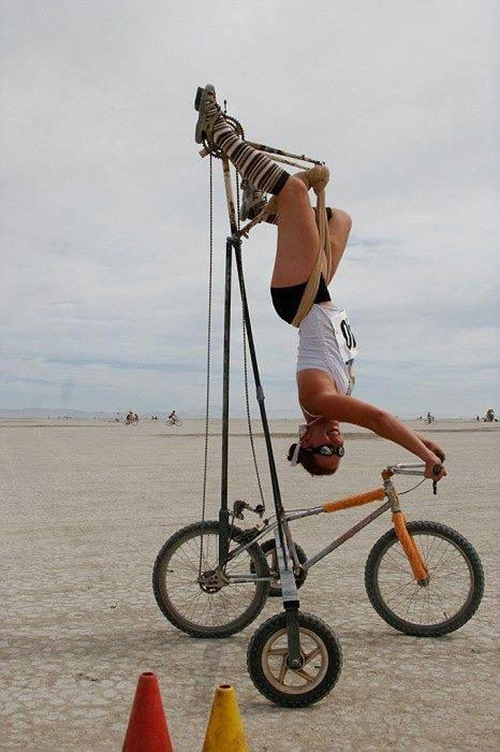 Ragazza a testa in giù su una bici al Burning Man