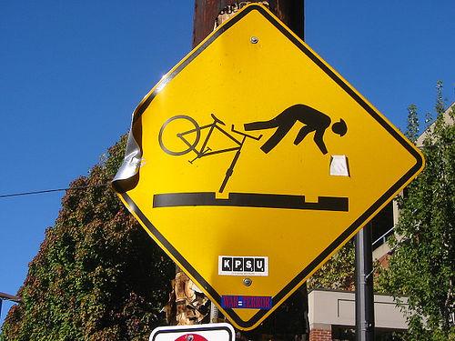 Un cartello di pericolo buche per ciclisti