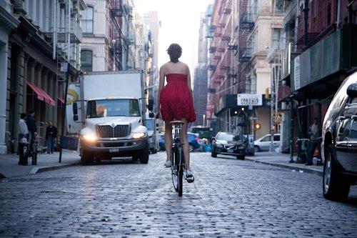Una ragazza in bici vestita di rosso