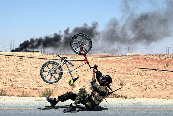 Un ribelle libico festeggia con la sua bici