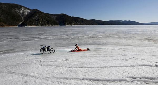 Ragazza prende il sole sulla neve con una bici al merendine