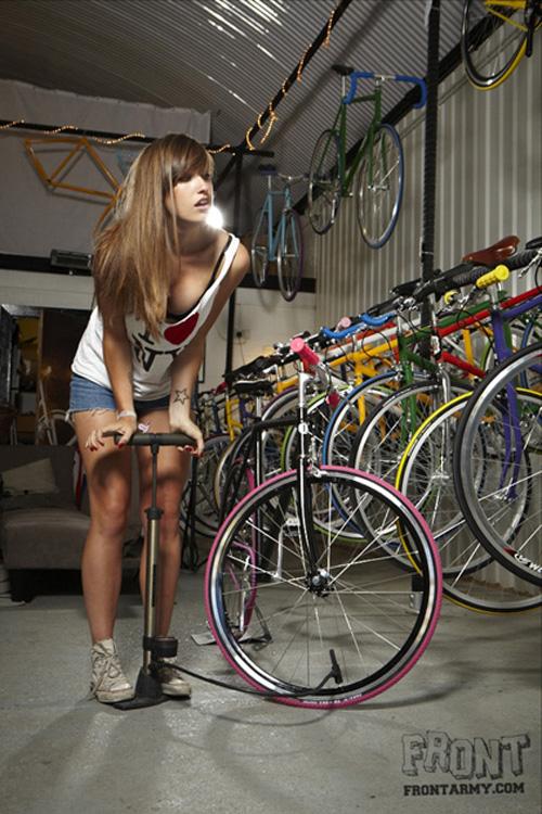 Ragazza che pompa una ruota di bicicletta