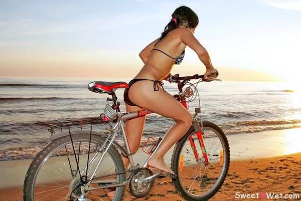 Una ragazza in bici in bikini sulla spiaggia