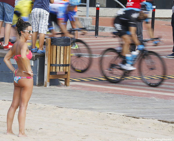 Una ragazza in bikini guarda una corsa ciclistica