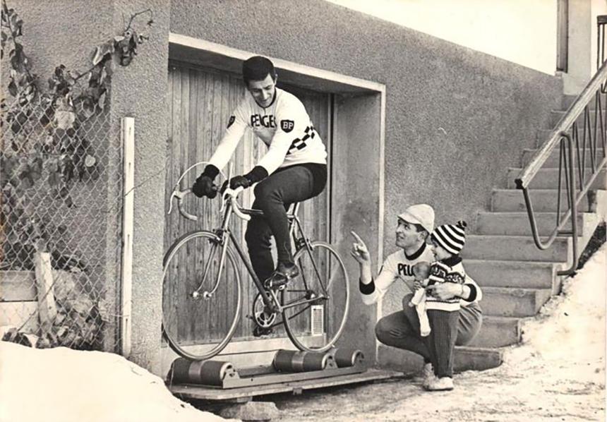 Ciclista su rulli liberi indicato da ciclista con bambino