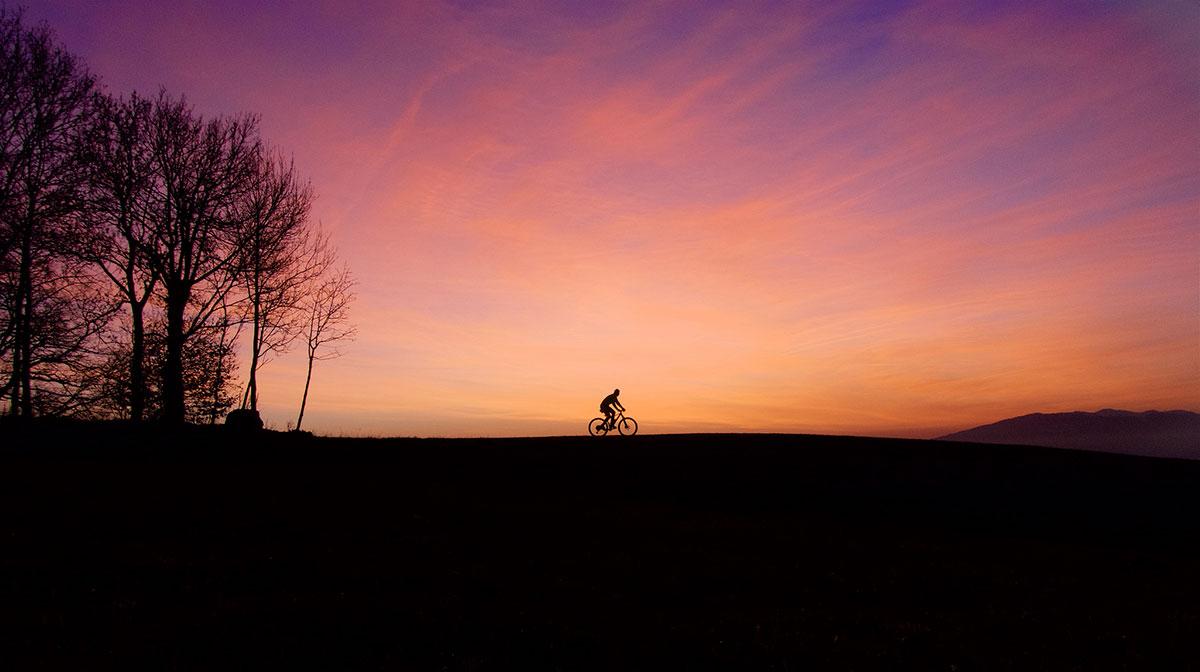 Ciclista solitario al tramonto
