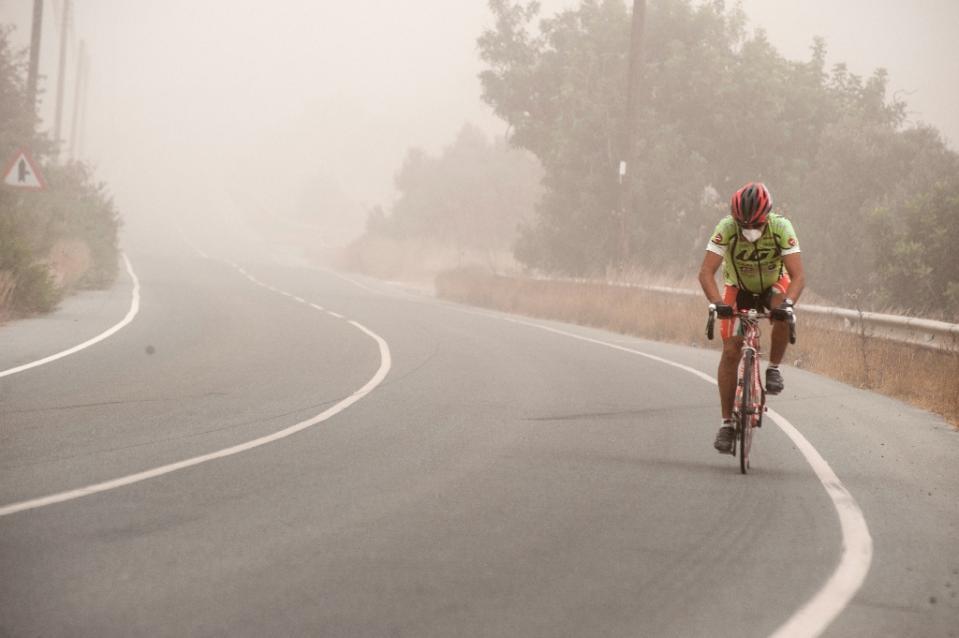 Ciclista a Cipro durante una tempesta di sabbia