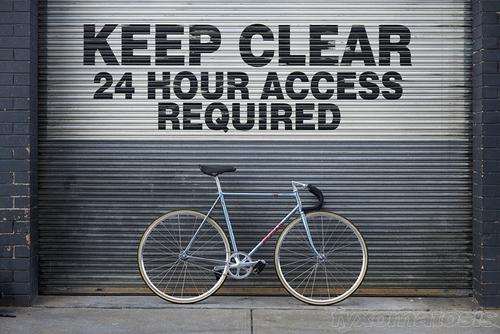 Una bici fissa davanti ad una saracinesca con l'avviso di tenere libero il passaggio