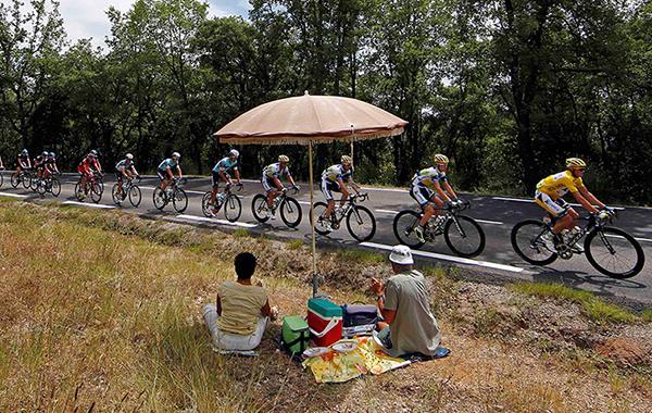 Turisti guardano il passaggio del Tour durante un picnic