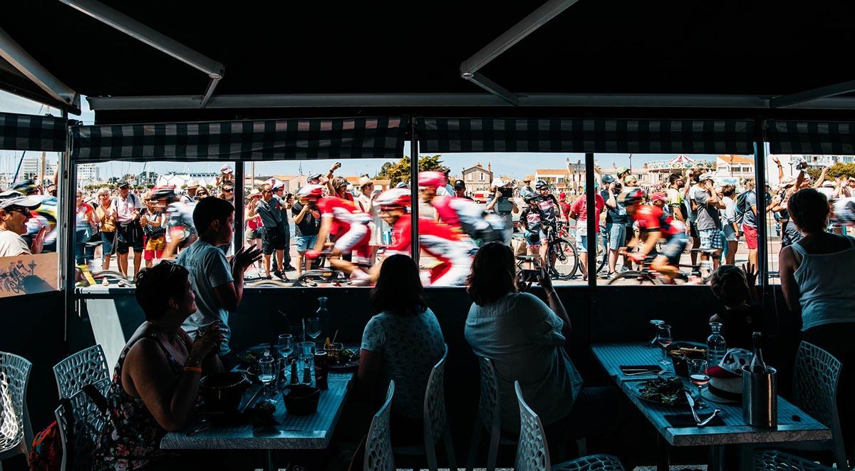 Spettatori guardano il Tour 2018 da un ristorante